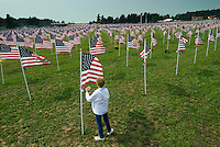 A woman reads the name tag attached to the corner flag in a field of 3,000 flags installed in a wheat field in Maria Stein, Ohio, Monday, September 11, 2006. The display was erected to honor military, police, fire fighters, and emergency workers on the anniversary of the attacks on the World Trade Center and Pentagon in 2001.<br />