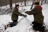 Kinder bauen eine Igel aus Schnee, Schnee wird aufgehäuft