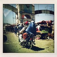 A woman in a burqa rides pillion on a motorbike through a vegetable market.