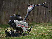 Twenty-year-old Craftsman tiller after clearing and ng fresh garden space for yard garden.