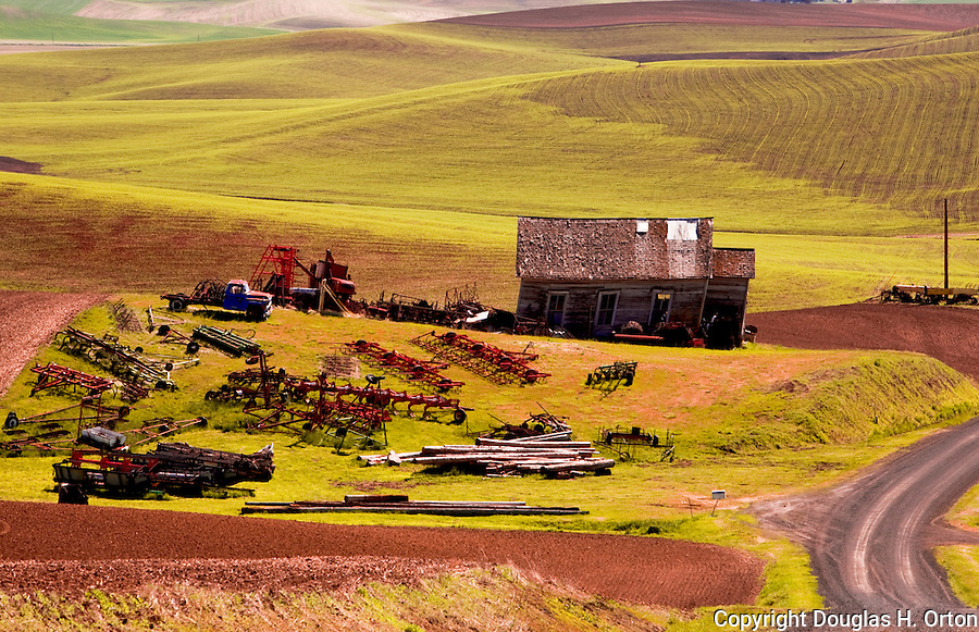 Palouse Hills, Washington, known as the heart of wheat farming in the United States is also famous for its rolling scenery.  This landscape featuring a farm machinery boneyard stored next to an abandoned home is at the base of Kamiak Butte, a Whitman County Park offering camping, picknicking, hiking, and incredible views of both Idaho and Washington Palouse country.