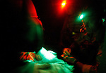 "2 US soldiers, wounded in an Improvised Explosive Deviece (IED) attack, are treated by a medic on a Medevac helicopter from the 101st Aviation Regiment as it flies a rescue mission at night to take them to Forward Operating Base Orgun-E in Paktika province, Afghanistan, 21 July, 2008. Also known by their call sign ""Dust Off"","" the Medevac pilots, crew and medics are ready to fly at a moments notice, picking up Coalition soldiers as well as Afghans that require help.(John D McHugh)"
