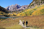Caucasian senior couple walking along Maroon Lake and Maroon Bells Peaks, near Aspen, Colorado, USA