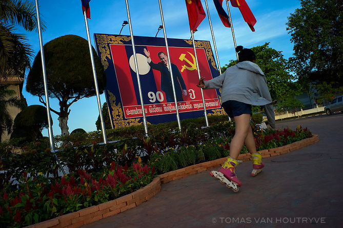 A girl on inline skates glides past a Communist poster showing the image of the first Communist leader of Laos, Kaysone Phomvihane, in Vientiane, Laos on March 20, 2011.