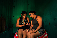 Salvadoran sex workers chat on the phone while waiting for clients in a room of a street sex bar in San Salvador, El Salvador, 13 April 2018. Although prostitution is not legal in El Salvador, dozens of street sex workers, wearing provocative miniskirts, hang out in the dirty streets close to the capital's historic center. Sex workers of all ages are seen on the streets but a significant part of them are single mothers abandoned by their male partners. Due to the absence of state social programs, they often seek solutions to their economic problems in sex work. The environment of street sex business is strongly competitive and dangerous, closely tied to the criminal networks (street gangs) that demand extortion payments. Therefore, sex workers employ any tool at their disposal to struggle hard, either with their fellow workers, with violent clients or with gang members who operate in the harsh world of street prostitution.