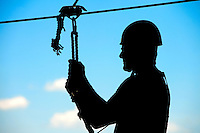 A silhouetted zip line participant prepares take flight and zoom through the air over the US National Whitewater Center (USNWC) on the USNWC's zip-lines, part of the facilities high-adventure offerings. The popular outdoor adventure activity lets outdoor enthusiasts be secured into a harness then propelled by gravity along an inclined steel cable. Charlotte, North Carolina's US National Whitewater Center offers two zip lines, which vary in height and distance traveled, as well as one of the largest outdoor climbing facilities in the world. The USNWC is a non-profit outdoor recreation facility open to the public for whitewater rafting, kayaking, canoeing, rappelling, zip lining, mountain biking, hiking, climbing and more. The center opened to the public in 2006.