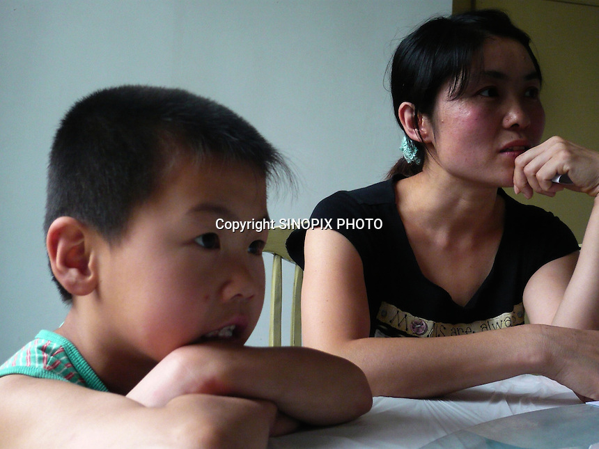 """Mrs Tian and her son Li Zhao Tian, 7 who suffers from blood cancer.  Xiditou village is known as one of China's worse """"cancer villages"""" where a reported ten percent have died from cancer."""