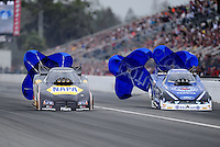Mar. 11, 2012; Gainesville, FL, USA; NHRA funny car driver Ron Capps (left) races alongside Robert Hight during the Gatornationals at Auto Plus Raceway at Gainesville. Mandatory Credit: Mark J. Rebilas-