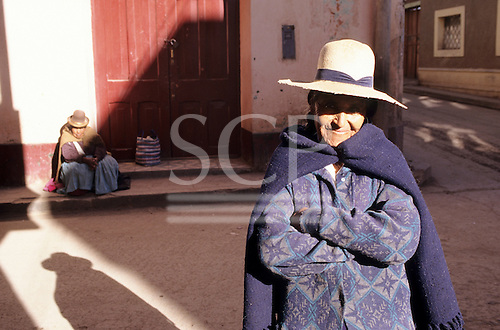 Paucartambo, Peru. A woman in traditional dress sitting in front of a closed door with another woman in the foreground.