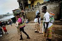 Marbella Slum, Freetown, Sierra Leone - women walking the street near the health centre