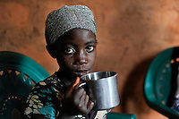 ANGOLA Kwanza Sul, rural development project ACM-KS, girl drinks water from cup in village Cassombo / ANGOLA Kwanza Sul, laendliches Entwicklungsprojekt ACM-KS, Dorf Cassombo, Maedchen trinkt Wasser aus einer Blechtasse