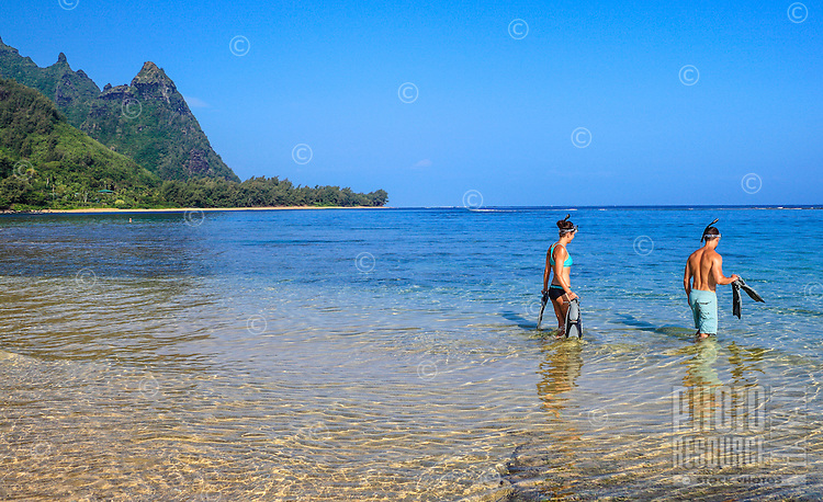 Snorkelers with their snorkeling gear wade into the clear waters at Tunnels Beach on Kaua'i.