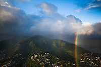 A view taken from an airplane at sunset of double vertical rainbows beaming down over Tantalus, with Manoa Valley in the distance on the right, O'ahu.