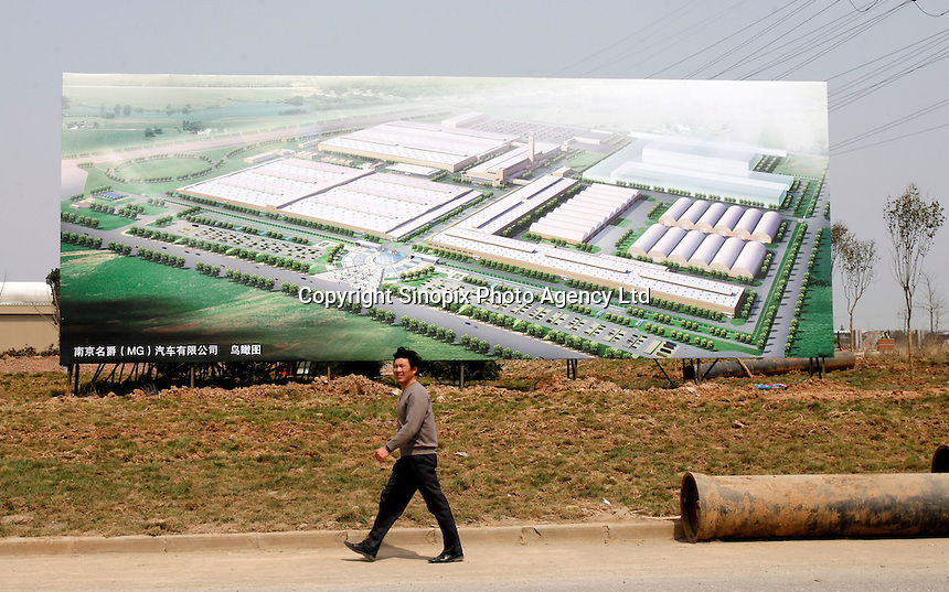 A man walks past a billboard showing an artist impression of the Nanjing MG Automobile plant in Nanjing, China. The Chinese company is now in a position to take on Rover's assets and plan its future. It intended to relocate the engine plant and some car production plant to China but to retain some car production plant in the UK..27 Mar 2007