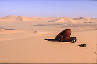 Libya, Tuareg men pray in the plain desert