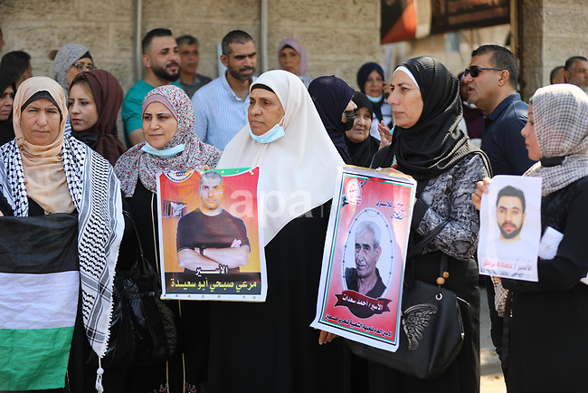 Palestinians take part in a protest to show solidarity with prisoners on hunger strike in Israeli Jails, in front of the headquarters of Red cross in Gaza city on August 09, 2021. A total of 13 Palestinian prisoners in Israeli detention currently remain on hunger strike in protest of their unfair administrative detention without a charge or trial, according to the Detainees and Ex-Detainees Affairs Commission. Photo by Ashraf Amra