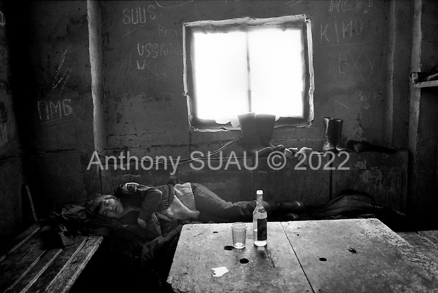 Lonya, Russia  .March 1999.A woman lays pasted out from drink at mid-day..