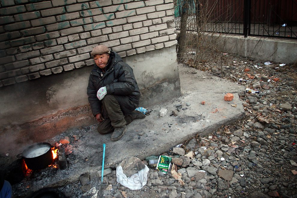 MONGOLIA. Ulaan Baatar. Battar, 55, waits for breakfast to cook on a bitterly cold winter morning. As the global financial crisis grips Asia, Mongolia is feeling the implications first hand as the country suffers from rising inflation pushing the price of food and fuel ever upwards. For the country's homeless, who live in sewers and abandoned garages in the capital and already face extreme discrimination and are denied access to basic health and social care, their lives are hanging in the balance. 2008