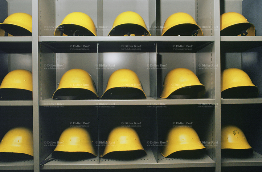 Switzerland. Canton Lucerne. A cabinet with yellow helmets in the Sonnenberg tunnel in Lucerne during the largest civil defense exercise ever held in the country. From 16 to 21 November 1987, almost 1200 men and women converted a motorway tunnel into perhaps the world's largest bunker structure. The civil protectors had to prove during the exercise «Ameise» ( Ants in english) that in an emergency more than 20,000 inhabitants of the city of Lucerne could survive here in the mountain for two weeks. The Sonnenberg Tunnel is a 1,550m  long motorway tunnel, constructed between 1971 and 1976. At its completion it was also the world's largest civilian nuclear fallout shelter, designed to protect 20,000 civilians in the eventuality of war or disaster. Based on a federal law from 1963, Switzerland aims to provide nuclear fallout shelters for the entire population of the country. The construction of a new tunnel near an urban centre was seen as an opportunity to provide shelter space for a large number of people at the same time. The giant bunker was built between 1970 and 1976 at a cost of 40 million Swiss francs. The shelter consisted of the two motorway tunnels (one per direction of travel), each capable of holding 10,000 people in 64 person subdivisions. A seven story cavern between the tunnels contained shelter infrastructure including a command post, an emergency hospital, a radio studio, a telephone centre, prison cells and ventilation machines. The shelter was designed to withstand the blast from a 1 megaton nuclear explosion 1 kilometer away. The blast doors at the tunnel portals are 1.5 meters thick and weigh 350 tons. The logistical problems of maintaining a population of 20,000 in close confines were not thoroughly explored, and testing the installation was difficult because it required closing the motorway and rerouting the usual traffic. The only large-scale test, a five-day exercise in 1987 to practice converting the road tunnels into usable shelters, rev