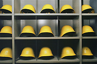 Switzerland. Canton Lucerne. A cabinet with yellow helmets in the Sonnenberg tunnel in Lucerne during the largest civil defense exercise ever held in the country. From 16 to 21 November 1987, almost 1200 men and women converted a motorway tunnel into perhaps the world's largest bunker structure. The civil protectors had to prove during the exercise «Ameise » ( Ants in english) that in an emergency more than 20,000 inhabitants of the city of Lucerne could survive here in the mountain for two weeks. The Sonnenberg Tunnel is a 1,550 m  long motorway tunnel, constructed between 1971 and 1976. At its completion it was also the world's largest civilian nuclear fallout shelter, designed to protect 20,000 civilians in the eventuality of war or disaster. Based on a federal law from 1963, Switzerland aims to provide nuclear fallout shelters for the entire population of the country. The construction of a new tunnel near an urban centre was seen as an opportunity to provide shelter space for a large number of people at the same time. The giant bunker was built between 1970 and 1976 at a cost of 40 million Swiss francs. The shelter consisted of the two motorway tunnels (one per direction of travel), each capable of holding 10,000 people in 64 person subdivisions. A seven story cavern between the tunnels contained shelter infrastructure including a command post, an emergency hospital, a radio studio, a telephone centre, prison cells and ventilation machines. The shelter was designed to withstand the blast from a 1 megaton nuclear explosion 1 kilometer away. The blast doors at the tunnel portals are 1.5 meters thick and weigh 350 tons. The logistical problems of maintaining a population of 20,000 in close confines were not thoroughly explored, and testing the installation was difficult because it required closing the motorway and rerouting the usual traffic. The only large-scale test, a five-day exercise in 1987 to practice converting the road tunnels into usable shelters, rev
