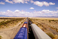 Two trains pass (one is on siding) on the Southern Pacific Railroad. Mount Graham on the right and the Dos Cabezas Mountain Range is on the left. railroads, transportation, desert landscape. Trains. Arizona.