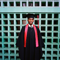 Emanuel, a 32-year-old student of businness and administration, who has just attended his graduation ceremony, stands in his gown and motar board at the Agostinho Neto University (Universidade Agostinho Neto).