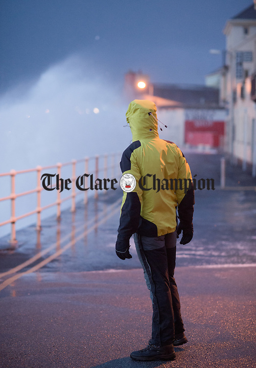 A man stands and waits his chance to make his way along the promenade in Lahinch during Storm Imogen. Photograph by John Kelly.