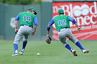 Outfielder Fred Ford (19) and second baseman Ramon Torres (12) of the Lexington Legends zero in on a pop fly that fell for a single in a game against the Greenville Drive on Friday, August 18, 2013, at Fluor Field at the West End in Greenville, South Carolina. Ford is the No. 23 prospect of the Kansas City Royals. Lexington won, 5-0. (Tom Priddy/Four Seam Images)