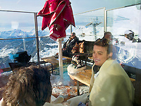 """Switzerland. Canton Valais. Tourists seat on a restaurant terrace in Verbier at """" Les Ruinettes"""" ( 2200 meters). Verbier is a village located in the municipality of Bagnes in the Val de Bagnes. Verbier is one of the largest holiday resort and ski areas in the Swiss Alps. Sunny day. Cable car. 3.01.2012 © 2012 Didier Ruef"""