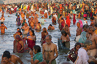 India. Uttar Pradesh state. Allahabad. Maha Kumbh Mela. A crowd of Indian Hindu devotees at sunrise in Sangam where people take holy dips. The Kumbh Mela, believed to be the largest religious gathering is held every 12 years on the banks of the 'Sangam'- the confluence of the holy rivers Ganga, Yamuna and the mythical Saraswati. In 2013, it is estimated that nearly 80 million devotees took a bath in the water of the holy river Ganges. The belief is that bathing and taking a holy dip will wash and free one from all the past sins, get salvation and paves the way for Moksha (meaning liberation from the cycle of Life, Death and Rebirth). Bathing in the holy waters of Ganga is believed to be most auspicious at the time of Kumbh Mela, because the water is charged with positive healing effects and enhanced with electromagnetic radiations of the Sun, Moon and Jupiter. The Maha (great) Kumbh Mela, which comes after 12 Purna Kumbh Mela, or 144 years, is always held at Allahabad. Uttar Pradesh (abbreviated U.P.) is a state located in northern India. 8.02.13 © 2013 Didier Ruef