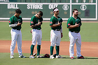 (L-R) Greenville Drive infielders Brandon Howlett (35), Christian Koss (8), Nick Yorke (4) and Joe Davis (34) pause for the National Anthem in a game against the Hickory Crawdads on Sunday, August 29, 2021, at Fluor Field at the West End in Greenville, South Carolina. (Tom Priddy/Four Seam Images)