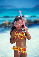 A young girl (age 6) prepares to have fun snorkeling in the warm blue waters of Oahu.