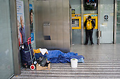 A homeless man sleeps in the entrance to a bank in Granada, Spain.