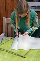 Kinder basteln ein Fensterbild mit Blüten, Mädchen schneidet Pergamentpapier in die richtige Größe