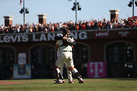 SAN FRANCISCO, CA - OCTOBER 3:  Dominic Leone #52 of the San Francisco Giants celebrates and hugs Buster Posey #28 after striking out San Diego Padres batter Eric Hosmer #30 for the final out in the top of the 9th inning to record the Giants 107th win of the season and clinch the National League West title at Oracle Park on Sunday, October 3, 2021 in San Francisco, California. (Photo by Brad Mangin)
