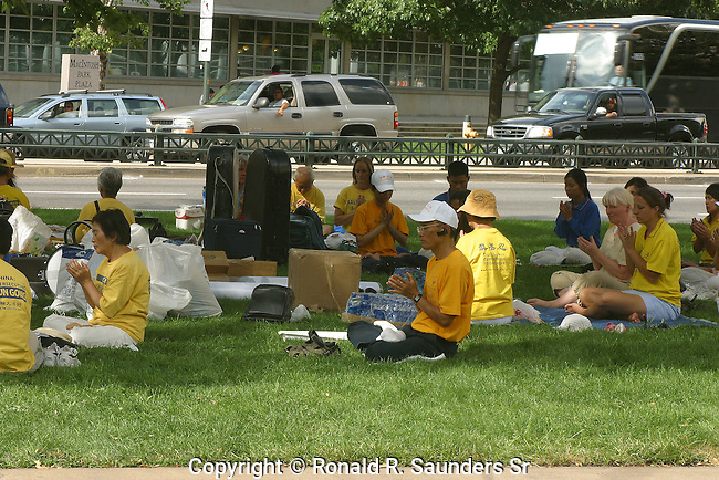 FALUN GONG MEMBERS SIT and PRAY on the PARK at DENVER.It is a movement of spirtuality that began in China in 1992 and based on the teachings and practices of both Buddhist and Taoist doctrines. Some call it a religion while others insist it's a cult.
