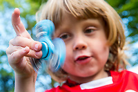 A young boy in a red school uniform plays with a blue fidget spinner toy