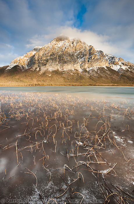Frozen pond in the foreground of mt Dillon of the Brooks Range mountains with afternoon sun highlighting the rugged rocky face, Alaska