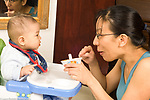 Six month old baby boy in high chair seat watching as mother points at dish of food he is about to eat horizontal Asian Chinese