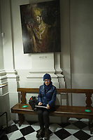 Switzerland. Canton Ticino. Lugano. Via Nassa. Church San Carlo Borromeo (Chiesa di San Carlo Borromeo). A woman is seated on a wooden bench and checks the picture she took with her iPad tablet. On the wall, an oil painting of Carlo Borromeo by Emmanuele Gregolin ( 2008). Charles Borromeo (Italian: Carlo Borromeo, 2 October 1538 – 3 November 1584) was the Archbishop of Milan from 1564 to 1584 and a cardinal of the Catholic Church. He was a leading figure of the Counter-Reformation combat against the Protestant Reformation. In that role he was responsible for significant reforms in the Catholic Church, including the founding of seminaries for the education of priests. He is honored as a saint by the Catholic Church, with a feast day on November 4. <br /> 16.12.2020  © 2020 Didier Ruef