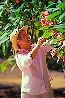 Elderly asian woman gardening in her yard
