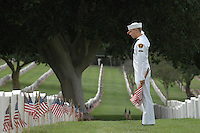 Saturday, May 22, 2009.  Fort Rosecrans National Cemetery, San Diego California, USA:  Cadet George Mick (15) of the Miramar based United States Naval Cadet Corps salutes after placing a flag at grave sites in the Fort Rosecrans National Cemetery.  Hundreds of boy scouts, girl scouts and their parents fanned out across the cemetery to plant flags at each grave site to mark Memorial Day..