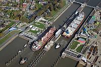 Nord Ostseekanal Schleuse Brunsbuettell: EUROPA, DEUTSCHLAND, SCHLESWIG-HOLSTEIN, BRUNSBUETTEL , (EUROPE, GERMANY), 19.10.2018: Schleuse Nord-Ostseekanal von Brunsbuettel. Der Nord-Ostsee-Kanal (NOK; internationale Bezeichnung: Kiel Canal) verbindet die Nordsee (Elbmuendung) mit der Ostsee (Kieler Foerde). Diese Bundeswasserstraße ist nach Anzahl der Schiffe die meistbefahrene kuenstliche Wasserstraße der Welt.<br /> Der Kanal durchquert auf knapp 100 km das deutsche Bundesland Schleswig-Holstein von Brunsbuettel bis Kiel-Holtenau und erspart den etwa 900 km laengeren Weg um die Nordspitze Daenemarks durch Skagerrak und Kattegat.<br /> Die erste kuenstliche Wasserstraße zwischen Nord- und Ostsee war der 1784 in Betrieb genommene und 1853 in Eiderkanal umbenannte Schleswig-Holsteinische Canal. Der heutige Nord-Ostsee-Kanal wurde 1895 als Kaiser-Wilhelm-Kanal eroeffnet und trug diesen Namen bis 1948. Zwei Frachtschiffe fahren unter Schlepperhilfe in die Schleuse.