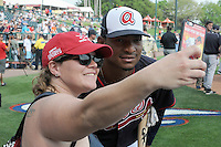 Catcher Christian Bethancourt (27) of the Atlanta Braves poses for a selfie with a fan before a Spring Training game against the New York Yankees on Wednesday, March 18, 2015, at Champion Stadium at the ESPN Wide World of Sports Complex in Lake Buena Vista, Florida. The Yankees won, 12-5. (Tom Priddy/Four Seam Images)