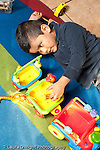 Education preschool 3-4 year olds boy on floor playing by himself with plastic vehicle and human figures talking to self  vertical