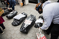 NEW YORK, UNITED STATES - NOVEMBER 21: An activist organizes a plastic bag as if it were a dead body on November 21, 2020 in New York City. Some people gather in Columbus Circle to protest against the government of President Donald Trump, with a symbolic act where they use black bags as if they were corpses due to the thousands of deaths produced by Covid-19. Photo by Pablo Monsalve / VIEWpress via Getty Images)