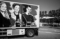 Switzerland. Canton Fribourg. La Rose de la Broye, near the village of Lully, on the A1 highway. A truck from the transport and logistics company Traveco is parked on the resting area. Smiling faces of two young women and a man are drawn on a truck's trailer. (Left to right ) A secretary holding a binder, a forklift driver and a mechanic with a wrench in his hand. A derelict Mirage plane, which was a military fighter aircraft, is fixed on the ground as a decorated monument. Mirage is a name given to several types of jet aircraft designed by the French company Dassault Aviation (formerly Avions Marcel Dassault), some of which were produced in different variants. Most were supersonic fighters with delta wings. 24.06.2020 © 2020 Didier Ruef