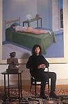 """Ivor Braka  art dealer at home, with David Hockney on wall """"The Room, Tarzana, 1967""""  1990s UK"""