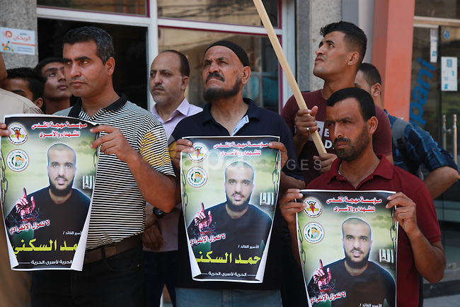 Palestinian supporters of the Islamic Jihad Movement, take part in a support with prisoner Ahmed Al-Sakani on hunger striker in Israeli Jails, in Gaza city on August 10, 2021. A total of 13 Palestinian prisoners in Israeli detention currently remain on hunger strike in protest of their unfair administrative detention without a charge or trial, according to the Detainees and Ex-Detainees Affairs Commission. Photo by Omar Ashtawy