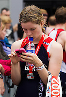 10 AUG 2014 - LIVERPOOL, GBR - Kayleigh Adams (age group category 17-19) checks her mobile phone after completing the Tri Liverpool triathlon which incorporated the 2014 British Age Group Triathlon Championships in Kings Dock in Liverpool, Great Britain (PHOTO COPYRIGHT © 2014 NIGEL FARROW, ALL RIGHTS RESERVED)